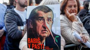"""""""Babiš i en fälla"""" står det på det här plakatet som föreställer Babiš med lång näsa."""