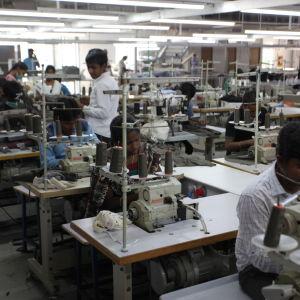 Textilarbetare syr ihop tröjor i fabrik.