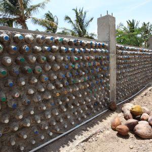 Mur med infogade plastflaskor som går runt en sandig gård.