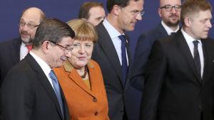 Turkiets premiärminister Ahmet Davotoglu och Tysklands förbundskansler Angela Merkel samtalar under EU-toppmötet den 7 mars.