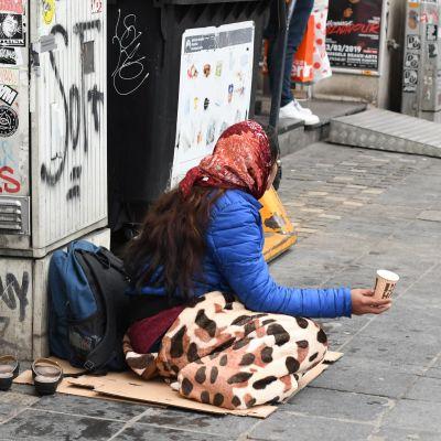 Kvinna tigger på gata.