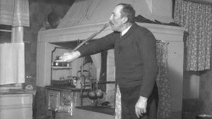 """En man leker leken """"pussa käppen"""", där han kysser ändan av en käpp som han håller i ena handen. Bilden är tagen 1938 i Närpes, Näsby."""
