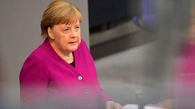 Angela Merkel talar framför ett talarpodium. Hennes reflektion syns på bildens högra sida.