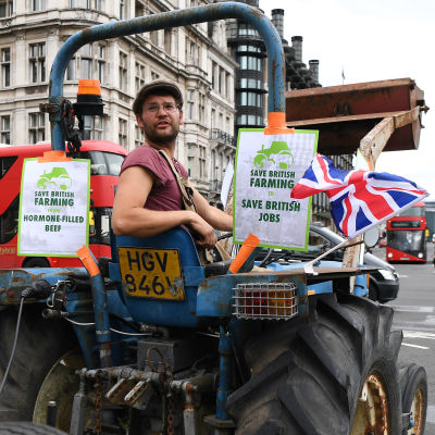 Mies ajaa traktorilla, johon on kiinnitetty Britannian lippuja ja iskulauseita.