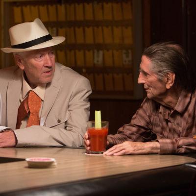 De gamla vännerna Lucky och Howard inbegripna i samtal i baren.