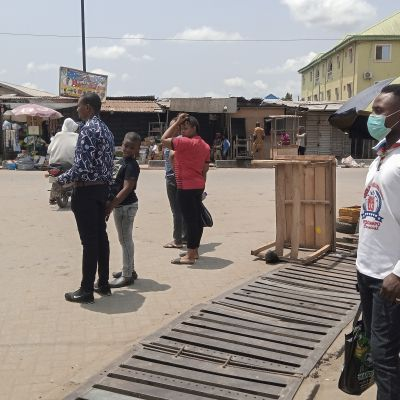 En man väntar på bussen i Lagos i Nigeria och bär en ansiktsmask. Coronaviruset har i början av mars 2020 nått NIgeria.