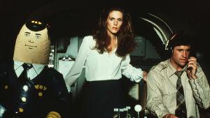 Elaine Dickinson (Julie Hagerty) och Ted Striker (Robert Hays) i cockpiten tillsammans med en så kallad uppblåsbar autopilot.