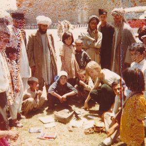 1970-luvun kuvassa nuori Jussi Nissinen on levittänyt tavaroitaan kadulle Kabulissa. Ympärille on kerääntynyt ihmettelevien miesten ja lasten piiri.