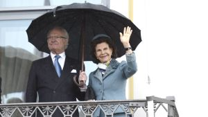 Kung XVI Gustaf och drottning Silvia vinkar från balkongen på presidentens slott.