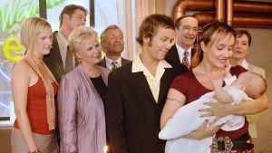 Hessu (Petteri Jaamalainen) ja Danny (Anni Turunen) kastavat lapsensa. Danny pitää lasta sylissä, muu juhlaväki katsoo lasta heidän selkänsä takaa.