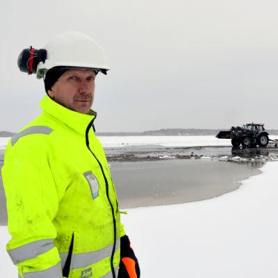Yngve Sundström håller i trådarna för muddringen på Stadsfjärden i Vasa. Här står han på isen iförd en neongul arbetsmundering och hjälm. I bakgrunden ser man en traktor.