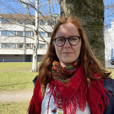 En kvinna med rött, axellångt hår tittar rätt in i kameran med allvarsam min. I bakgrunden syns ett höghus och några träd.
