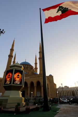 En jättelik libanesisk flagga vajar framför en Ramadan-lampa utanför Al Ameenmoskén i Beirut