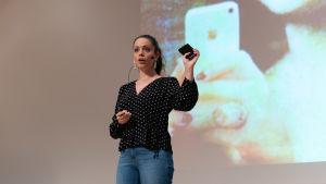 Felicia Margineanu håller en telefon i handeln framför en bild på Monalisa.