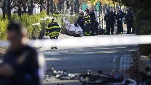 Räddningspersonal för bort ett av dödsoffren från cykelvägen där attacken inträffade.