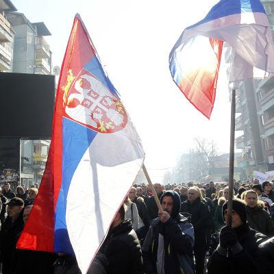Serber i Kosovo demonstrerar med serbiska flaggor och symboler på gata i staden Mitovica.