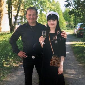 Mustiin pukeutunut isä ja ylioppilaslakki päässään oleva tytär aurinkoisen vihreällä pihalla