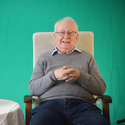 Allan Blom sitter i en fåtölj framför ett grönt tyg.