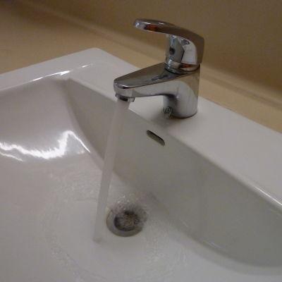 En vit badrumslavoar och en kran med rinnande vatten.
