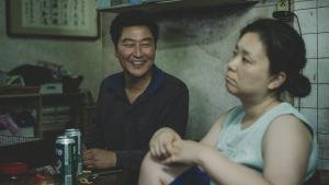 Kim Ki-taek (Kang-ho Song) sitter vid ett bord och skrattar och ser på sin fru Kim Chung-sook (Hye-jin Jang) som sitter bredvid.