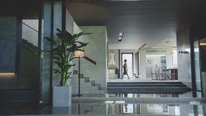 Ett stort vardagsrum med stora öppna ytor, i bakgrunden ser vi hembiträdet Moon-gwang (Jeong-eun Lee) gå in i köket med två hundar i släptåg.