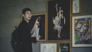 Kim Ki-woo (Woo-sik Choi) står bredvid en vägg med tavlor och ser förvånad ut.