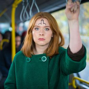 Rödhårig kvinna med kuk ritad i pannan står i en buss.