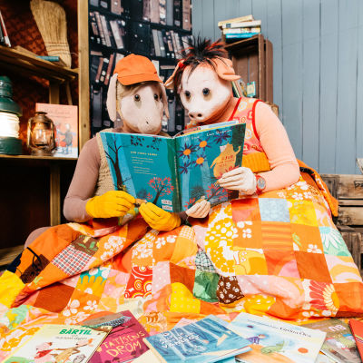 Bärtil och Isa Gris sitter under sagotäcket och läser