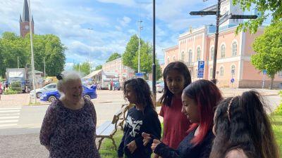 En äldre kvinna och sex flickor vid en bänk invid torget i Lovisa. De ser på varandra, talar och ler.