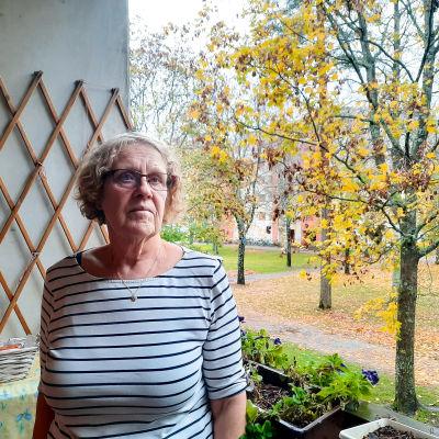 Äldre kvinna står på balkong och tittar förbi kameran. Bakom henne syns ett höstlandskap med träd och andra höghus.