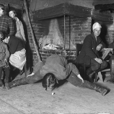 """En man leker leken """"ta spåna"""", där man stå så bredbent man kan och ta upp ett föremål från golvet utan att knäböja sig eller röra golvet med händerna. Bilden är tagen 1935 i Bromarf."""