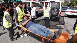 En skadad man bärs iväg på bår efter självmordsattacker i Afghanistans huvudstad Kabul.