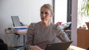 En kvinna som sitter vid ett skrivbord med en dator framför sig.