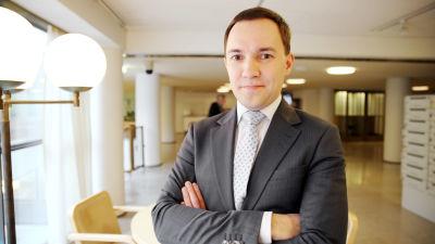 En ung man i grå kostym och ljus slips. På bilden riksdagsledamoten Wille Rydman.