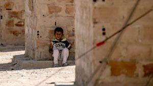 En liten pojke sitter i skuggan inne i lägret al-Hol 2.6.2019.