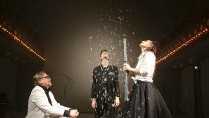 Tre skådespelare tittar upp mot vita fjun som singlar ner genom luften.