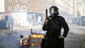 Polis med hjälm och gasmask håller ett vapen i handen och på gatan brinner något.