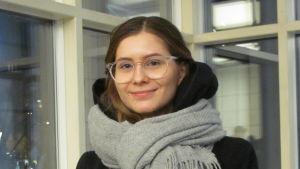 En ung kvinna med ljusbrunt hår och glasögon står framför ett fönster.