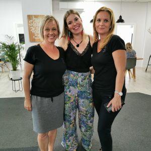 Kuvassa kolme naista, jotka hymyilevät.