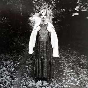 Nuori raskaana oleva nainen pitkässä mekossa puiden keskellä.