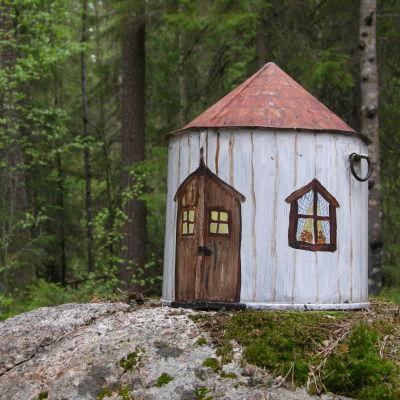 Ett leksakshus på en sten i skogen.