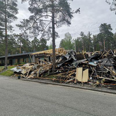 En bild på en radhuslänga som har brunnit ner. I bakgrunden syns ett grannhus som överlevt branden.