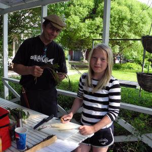 Isä Jukka ja tytär Viivi Vesanen laittavat ruokaa puutarhassa.