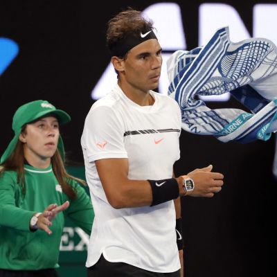 Rafael Nadal slänger sin handduk över axeln åt en bollpojke.