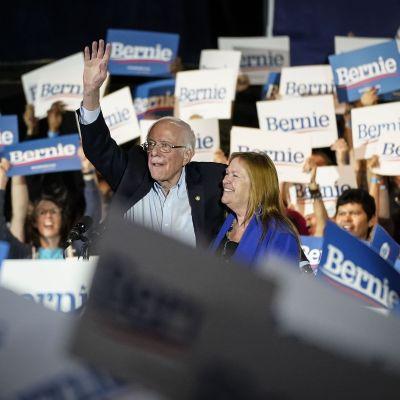 Bernie Sanders håller upp handen, hans fru ler bredvid. Runt honom glada anhängare men plakat det står Bernie på.