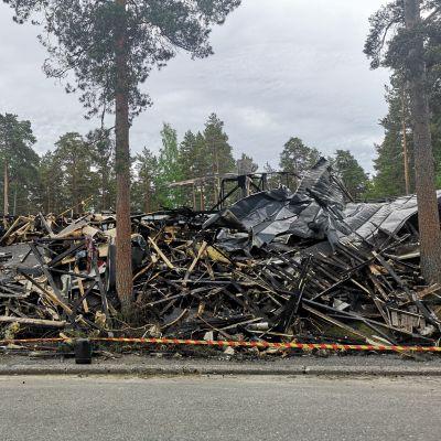 bild på hög med bränt trä och saker som brunnit upp i en brand i en radhuslänga.
