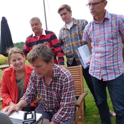 Markkinoinipäällikkö Niclas Gestranius, toimittaja Marcel Theroux ja suomalaiset kollegat ihastelevat valokuvaaja James Bedfordin ottamia saaristokuvia.