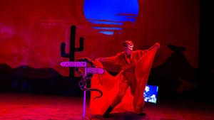 Skådespelaren Sue Lemström i turban och mantel står i ett nattligt ökenlandskap med en stor blå måne i bakgrunden.