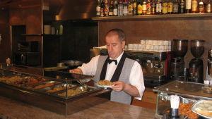 Tarjoilija annostelee tapaksia lautaselle baaritiskin takana espanjalaisravintolassa.