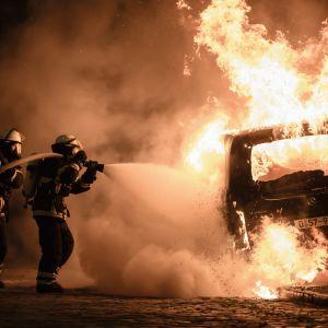 Brandmän släcker en brinnande bil i Hamburg den 8 juli under demonstrationerna kring G20-mötet.
